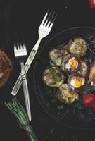 Mushrooms stuffed with quail eggs, on dark background photo