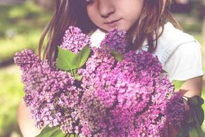 Little girl with bouquet of lilac in her hands photo