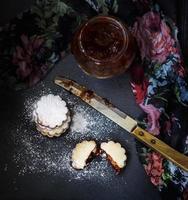 Vista superior de la pila de galletas caseras y tarro de mermelada, sobre fondo negro foto