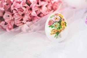 Huevo de pascua decorado en decoupage, con flores de jacintos rosas, sobre fondo de tul blanco foto