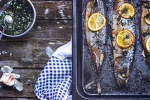 Three grilled fishes, on black baking tray, with copy space photo