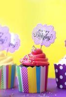 deliciosos cupcakes de fresa en coloridos vasos de papel para hornear, con tarjeta de felicitación de cumpleaños, sobre fondo amarillo. fondo de fiesta foto
