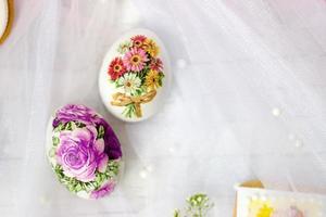 Huevos de Pascua decorados y flores sobre fondo de tul blanco técnica de decoupage foto