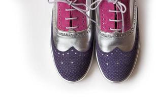 Vista superior de violeta, plata y rosa zapatos oxford de mujer, aislado sobre fondo blanco. foto