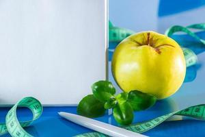 el concepto de dieta y nutrición adecuada. frutas y cinta métrica sobre un fondo azul. maquetación para el diseño. fin de cuarentena foto