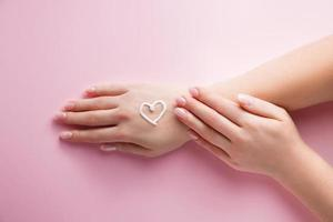Skin care concept. Woman is applying cream to her hands on pink background. Image for advertising and design. photo