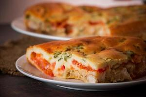 Homemade pie with chicken, herbs and tomatoes on a plate. photo