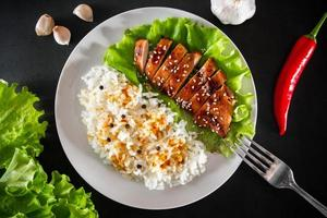 Teriyaki chicken with sesame seeds, lettuce and rice on a white plate. Dish with a fork on a black background photo