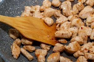 Pieces of chicken fillet fried in a pan. Cooking process. photo
