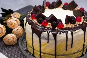 Beautiful festive cake with chocolate icing and marmalade on a background of flowers photo