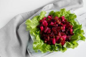 Russian salad vinaigrette on a gray background. Vegetarian dish with beets on a plate. photo