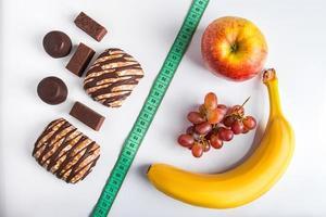 el concepto de elegir entre dieta y alimentos poco saludables. frutas frescas o dulces. foto