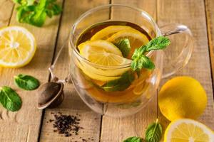 té de hierbas con limón y menta sobre fondo de madera. deliciosa bebida para la relajación y terapia alternativa de enfermedades. foto