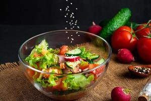 The process of preparing vegetable salad. Seasonal summer dish, vegetarian food on black background. photo
