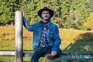 Cowboy in a denim jacket and hat near the fence in the mountains photo