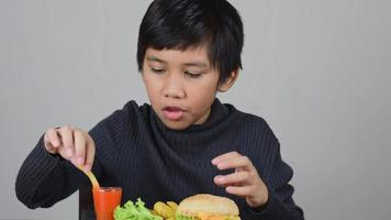 Cute Asian boy eating a delicious french fries with happiness video