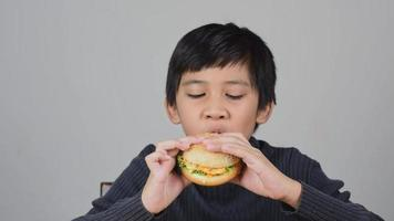 Cute Asian boy eating a delicious hamburger with happiness video