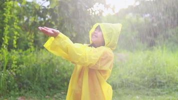 criança asiática brincando na chuva video
