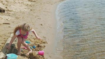 niños jugando en la playa junto al río en un día soleado video