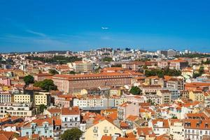 An airplane fly over lisbon, the capital city of portugal photo