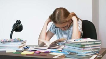 Ein Teenager-Mädchen mit Brille sitzt an einer Schulbank Lernkonzept video