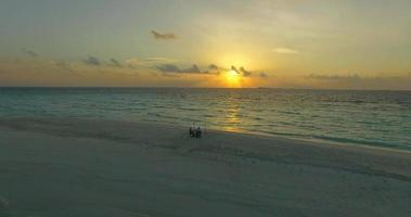 Aerial drone view of a man and woman eating dinner and dining on a tropical island beach. video