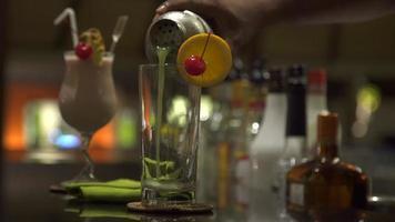 un barista versa un drink tropicale in un bar di un resort. video