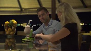 A man and woman couple have a drink at a bar at a resort. video