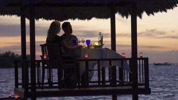 una pareja de hombre y mujer cenan y cenan en una cabaña en la playa de una isla tropical. video