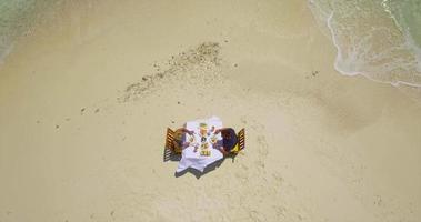 Aerial drone view of a man and woman eating breakfast on a tropical island sandbar beach. video
