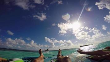 pov vista de un hombre y una mujer en un tubo inflable remolcando detrás de un bote a una isla tropical. video
