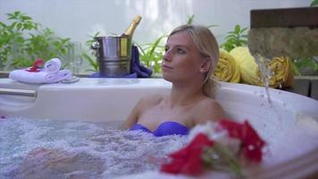 A woman bathing in a spa jacuzzi whirlpool bathtub hot tub. video