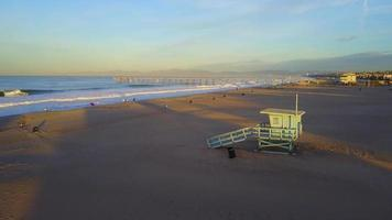 Aerial drone uav view of a lifeguard tower, pier, beach and ocean. video