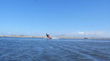ein Mann, der Kiteboarding macht und einen Sprungtrick auf einem Kiteboard macht. video