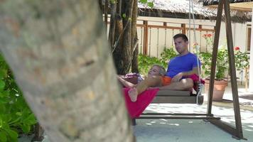 A couple on a hammock swing at a tropical island beach resort hotel. video