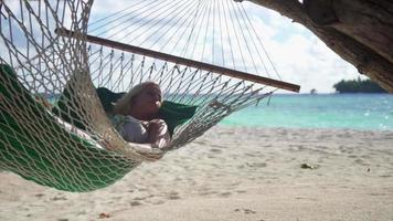 A woman lies on a rope hammock at a tropical island beach resort hotel. video
