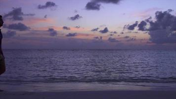 A couple walking on the beach at sunset at a tropical island resort hotel. video