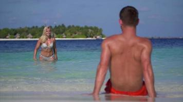 A playful woman splashes water on a man on the beach at a tropical island resort hotel. video