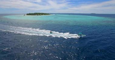 Aerial drone view of a man and woman on an inflatable tube towing behind a boat to a tropical island. video