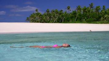 A woman floating in the ocean near a scenic tropical island beach in Fiji. video