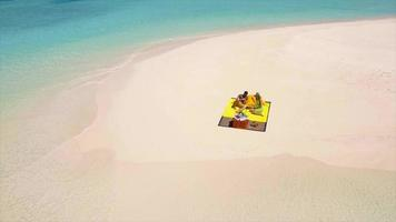 Aerial drone view of a man and woman couple having a picnic meal on a tropical island beach. video