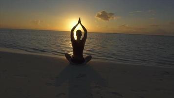 uma mulher faz uma pose de ioga sentada na praia com as mãos ao pôr do sol. video