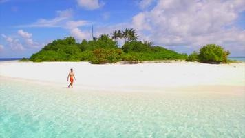 Aerial view of a man walking on the beach around a tiny deserted tropical island. video
