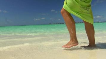 A woman wearing a sarong walks on the beach at a tropical island resort hotel. video