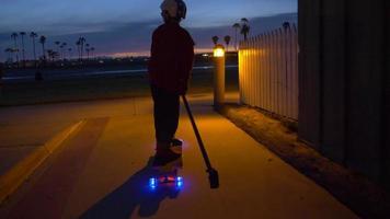 een jongen rijdt op een skateboard met led-verlichtingswielen in een buurt en een sup paddle-stick. video