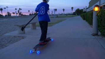 un niño monta una patineta con ruedas de luces led en un barrio y un palo de remo. video