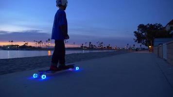 un niño monta una patineta con ruedas de luces LED en un vecindario. video
