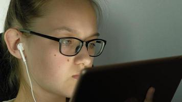 ragazza adolescente usa il tablet con le cuffie la sera video
