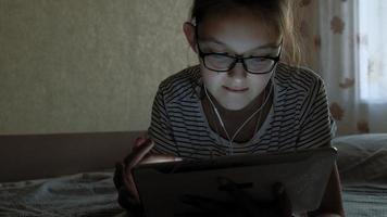 Teenager-Mädchen benutzt Tablet mit Kopfhörern abends video