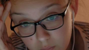 Teen girl uses tablet with headphones Evening time video